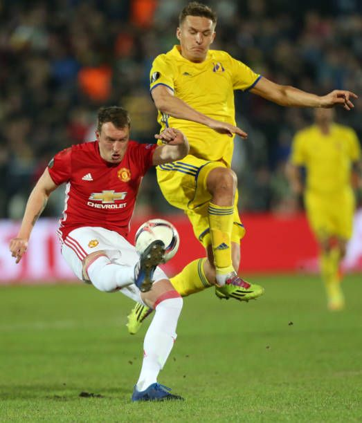 Phil Jones of FC Manchester United and Aleksandr Bukharov of FC Rostov vie for the ball during the UEFA Europa League Round of 16 first leg between...