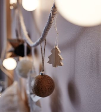A close-up image of ornaments and lights strung from a headboard.