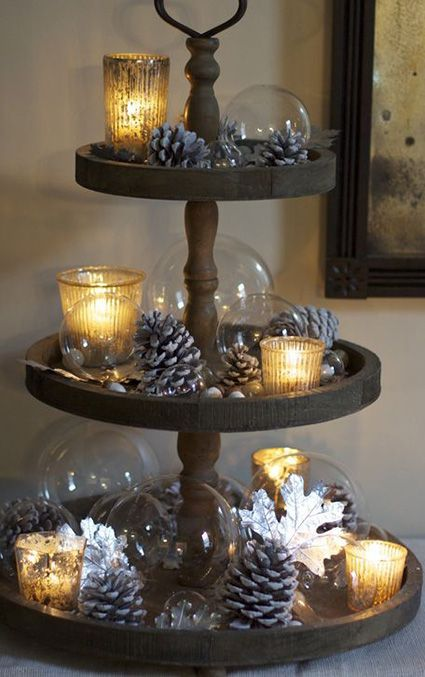 Use this Christmas centerpiece idea to mix together your classic and contemporary holiday decorations. Utilize a wooden 3-tiered stand to display snow-dusted pine cones, votive candles, and glass ornaments. Add a welcoming glow to your centerpiece by using gold mercury glass candle holders to hold your lights.