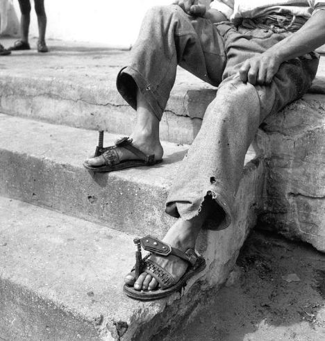 """Man's Shoes, Bo Kaap, 1942-3. Photographic image is a close-up of a man's sandals. The man is sitting on a step, his upper body cannot be seen in this image. Photograph by Constance Stuart Larrabee, 1942-3. The so-called """"Malay Quarter"""" in Cape Town, now Bo Kaap, was the home of South Africans whose forebears were brought by the Dutch East India Company to the region from the coasts of India and the Indonesian islands as convicts and slaves in the eighteenth century. The inhabitants of the…"""