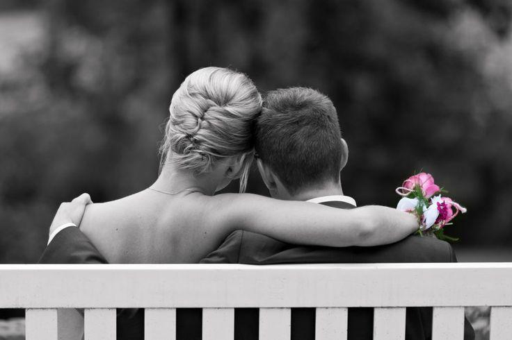 Bruidsfotografie Berry en Saskia op een bankje in de tuin van Kasteel Groot Buggenum in zwart-wit met een roze boeket