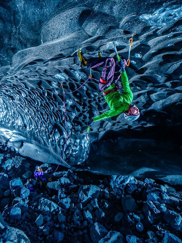 Picture of an ice climber hanging upside down in an ice cave in Iceland