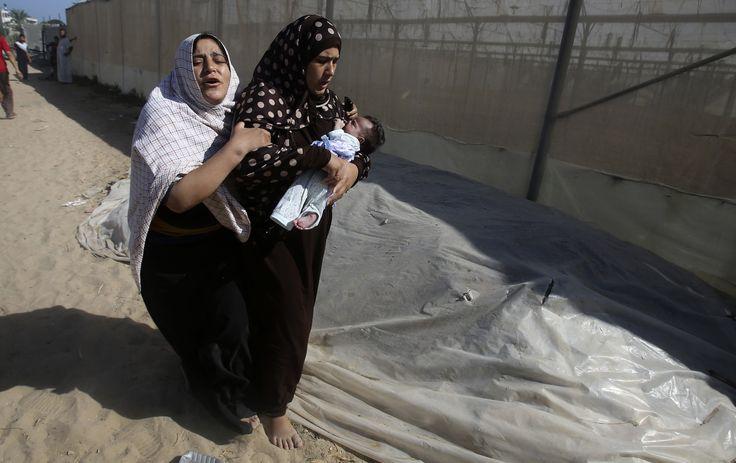Dua perempuan Palestina meninggalkan rumahnya bersama seorang bayi, saat serangan udara Israel melanda permukiman di Khan Younis, Jalur Gaza.