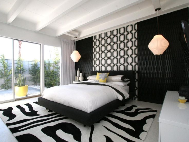 Here is a modern bedroom that opens to the great outdoors. The black and white bedroom is accented with retro lighting fixtures, bold patterns and a beamed ceiling.