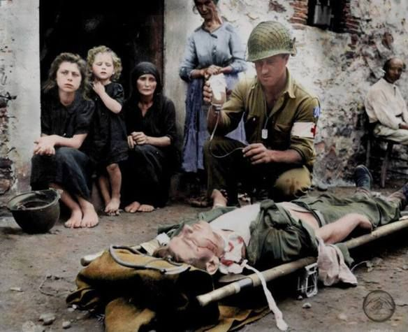 Colourized WWII photo : Pfc. Harvey White of Minneapolis gives blood plasma to a Pvt. Roy W. Humphrey from Toledo, Ohio of the 7th Inf. Regt., US 3rd Division at the aid station, Sant'Agata, Sicily, after he was wounded by shrapnel on the 9th August 1943  (Pvt. Humphrey was wounded near San Fratello and was later taken to the 93rd. Evacuation Hospital, where he recovered)