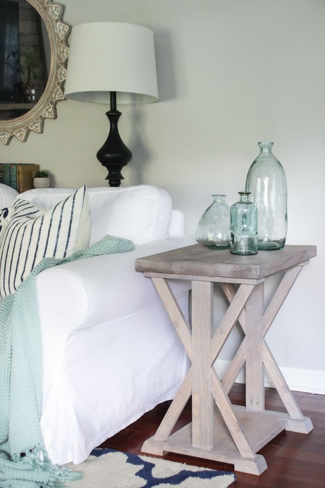 Farmhouse end table with X support legs, with blue glass bottles on top.