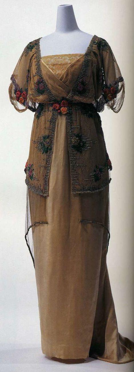 Вечернее платье. Поль Пуаре, 1910-1911. Платье из бежевого шелкового атласа с верхним платьем из шелкового тюля, вышивка разноцветным бисером и золотыми нитями, пеплум из золотистого тюля.