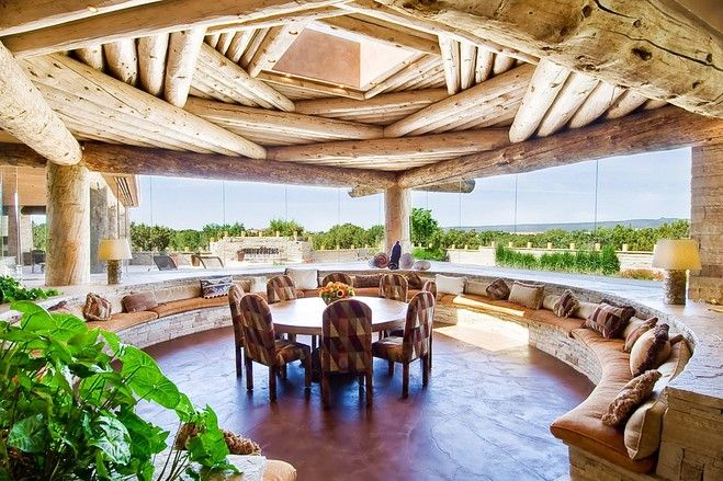 This CEILING is incredible!   This dining room is surrounded in large windows that overlook the property and features an intricate layering of vigas on the ceiling. The room, which was created by a previous owner, was inspired by a ceremonial area used by Pueblo peoples known as a kiva. Mrs. De Domenico added several recessed light fixtures in the ceiling and also upholstered the interior of the skylight well with leather.
