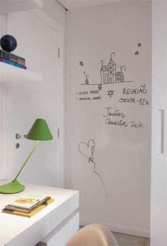 No quarto-escritório, ao lado do armário, uma lousa de laminado exibe anota...