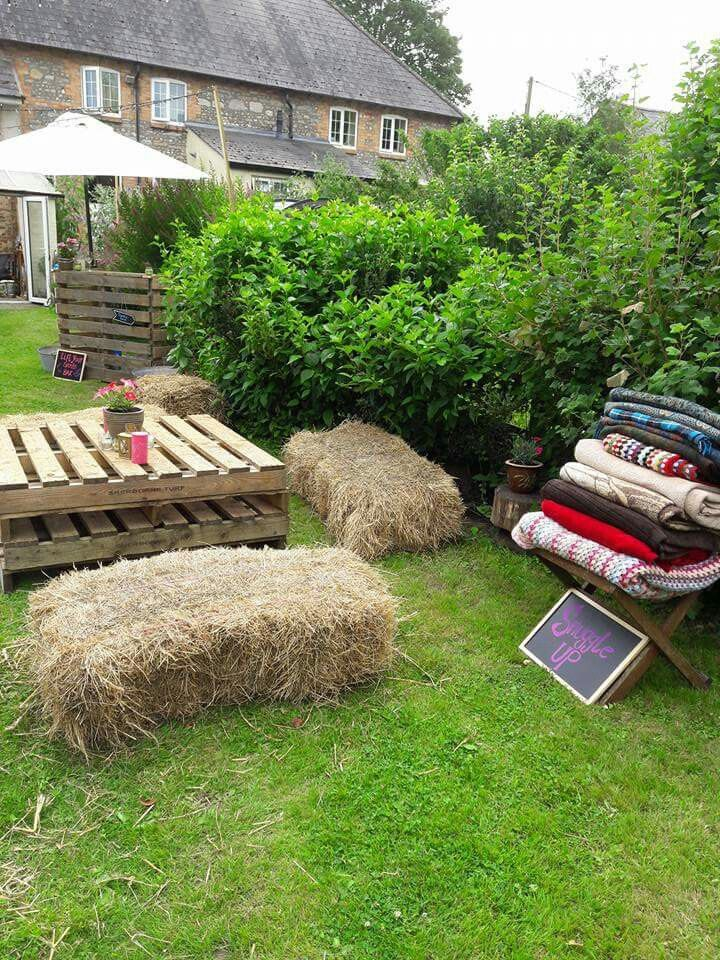 Pallets and Hay bales used to make garden party seating. Blankets to keep gusts warm when the sun goes down