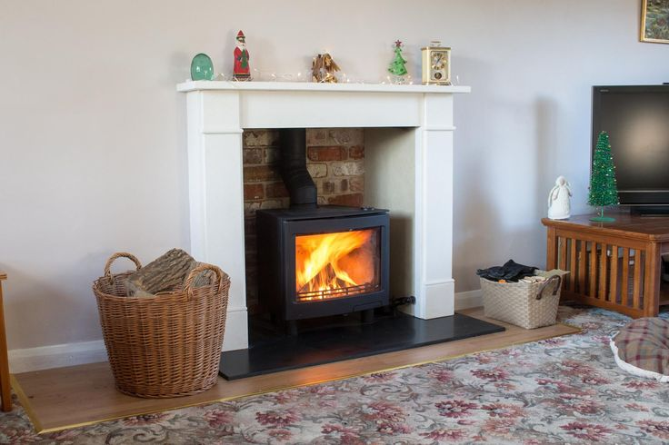 Contura i5 woodburning stove installed with a Limestone fireplace, granite hearth, fireproof board chamber with reclaimed brick feature wall.