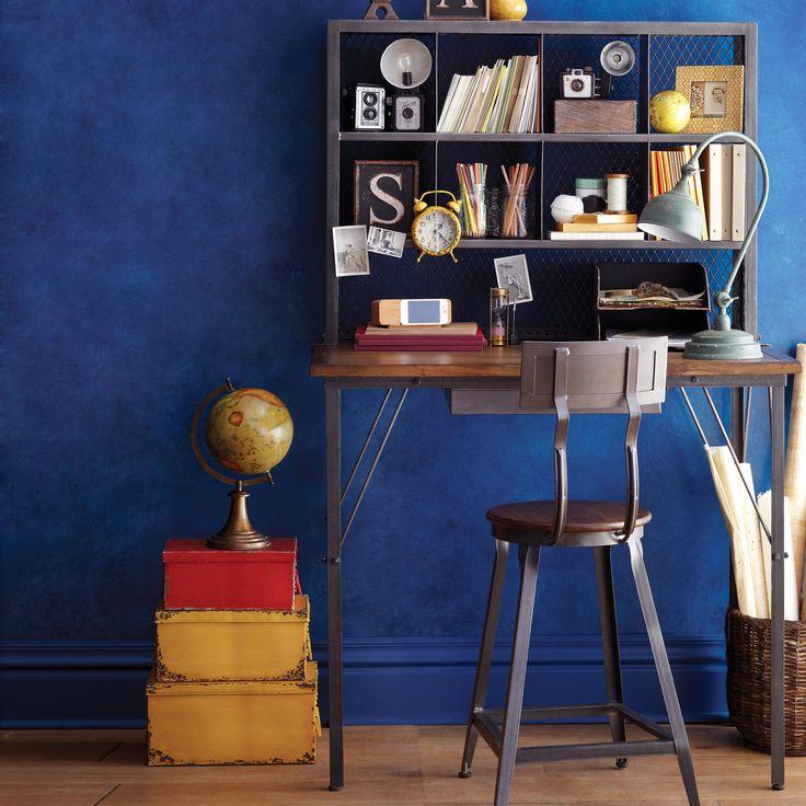 Il colore della parete la fa da padrone, ma anche la semplicità del piccolo scaffale a ridosso della scrivania...