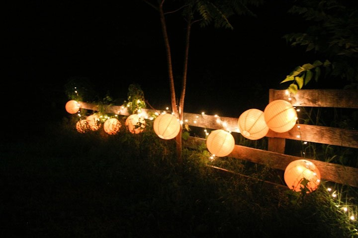 Lanterns with string lights on fence