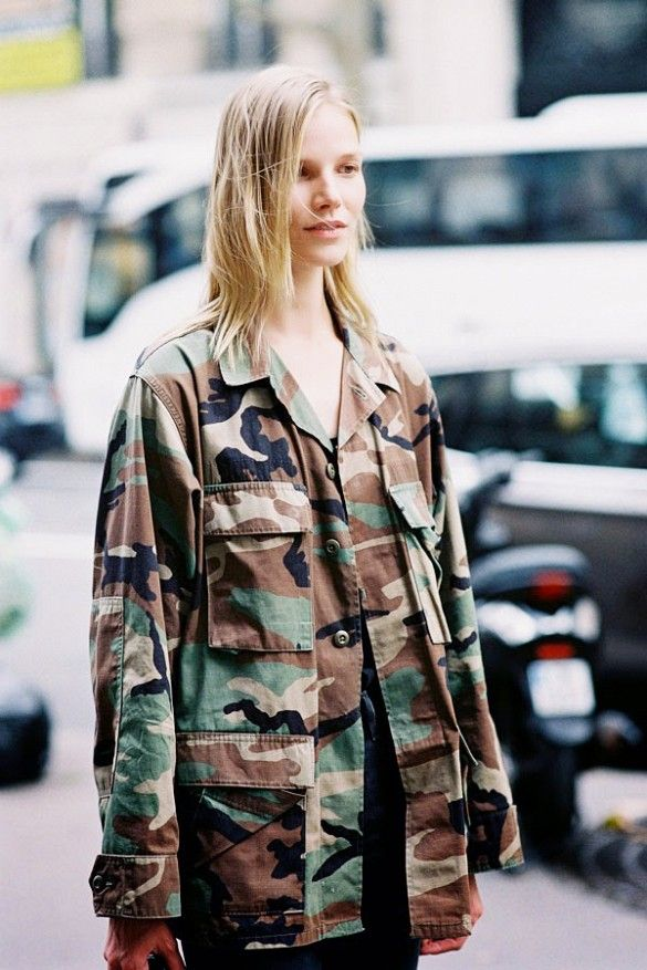 A army print jacket is worn over an all black ensemble.