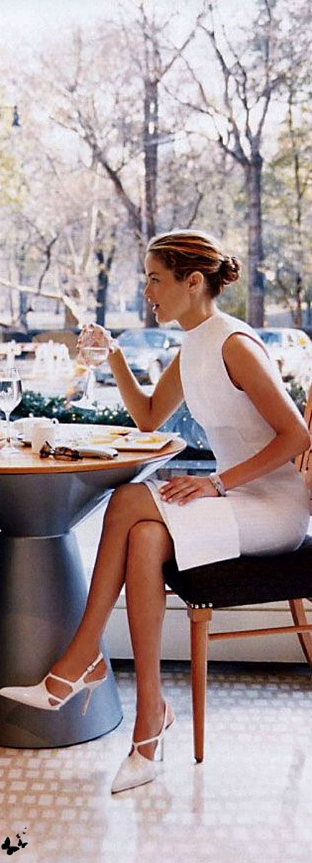 Chic and sophisticated in a white sheath dress, heels, and enjoying a cup of coffee.