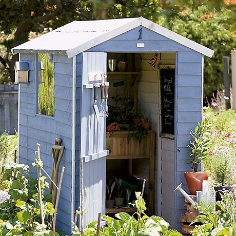 A pale blue and ivory shed situated in the centre of a