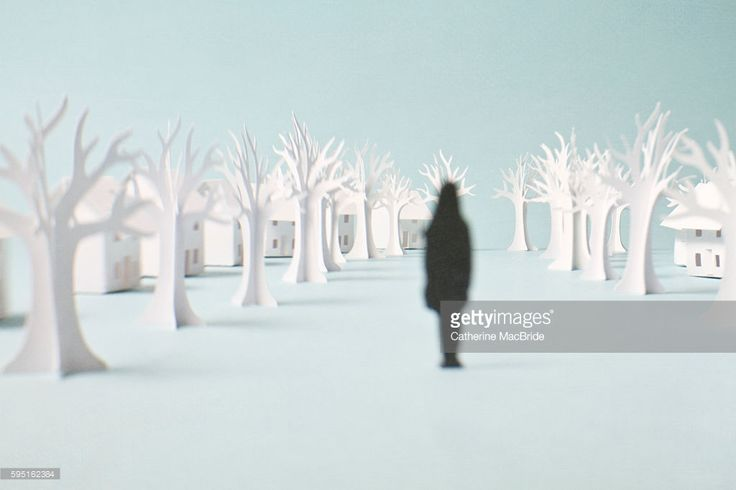 Paper art by Catherine MacBride, June 2013. A lone paper figure enters a tree lined paper street.