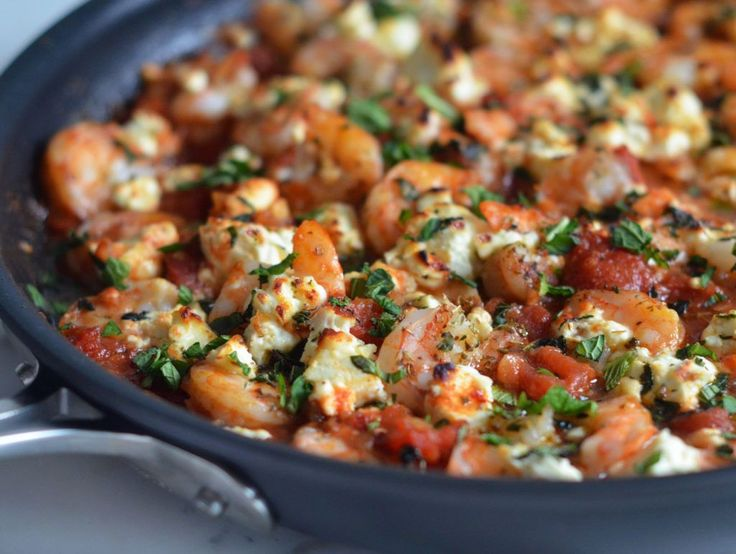 (TESTED & PERFECTED RECIPE) Shrimp nestled in a Greek-spiced tomato sauce, topped with chunks of feta, and then baked until golden.