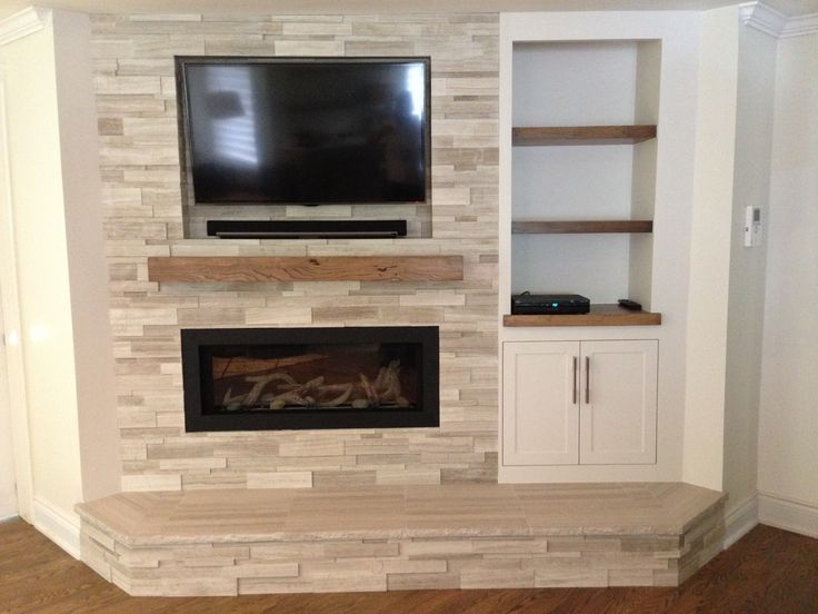 Stone fireplace with inlaid tv and custom shelving