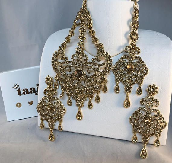 Matching earrings, tikka & jhumar set. Gold coloured earrings, tikka & jhumar with gold colour diamanté stones. Pierced ears only  Tikka L200mm xW40mm (max) tikka chain L130mm Earring L90mm x W40mm (max) Jhumar L150mm x W80mm (max)  ALL MEASUREMENTS ARE AN APPROXIMATION We put a great deal