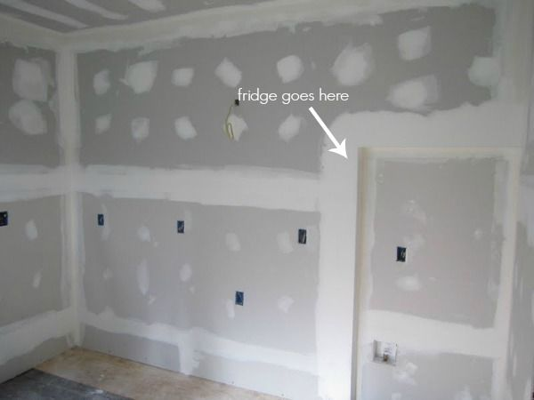 kitchen progress drywall. Homeowner recessed fridge into wall ~4' so it reads as a counter depth fridge.