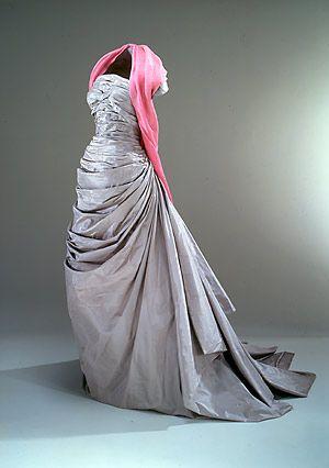 Stropløs hellang selskabskjole fra 1950'erne i silketaft med påsyet sjal med indvævede roser. (Nationalmuseet)