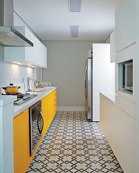"""Os moradores queriam uma cozinha colorida, mas que não cansasse. """"Optei pela laca brilhante amarela só nas portas do armário sob a bancada e deixei branco o de cima, na altura da visão"""", explica a arquiteta Andrea Reis. Para destacar a marcenaria, ela pin"""