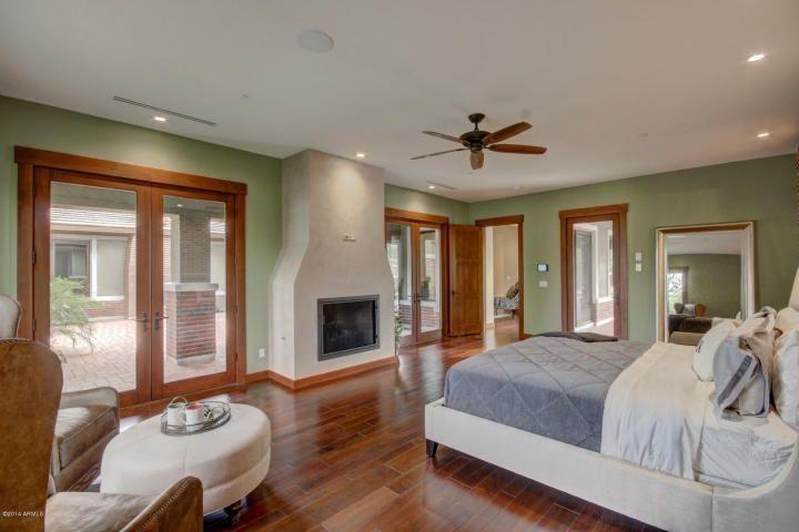 Craftsman Master Bedroom with specialty door, Cement fireplace, Pottery barn silver beaded floor mirror, Hardwood floors