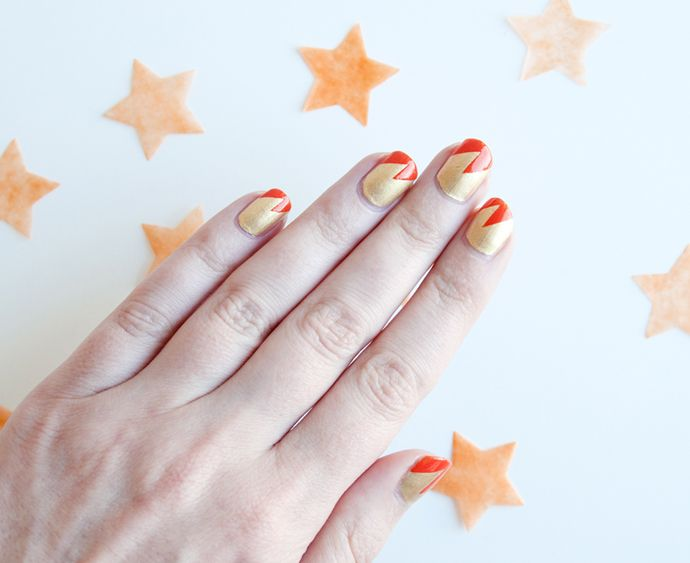 Gold and orange lighting bolt nail art.