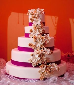 Wedding Cakes: Bright pink ribbon wedding cake with orange and white flowers
