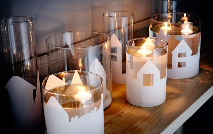 A close-up image of different sizes of IKEA CYLINDER vases, decorated with paper cutouts of landscapes, filled with water and a floating candle.