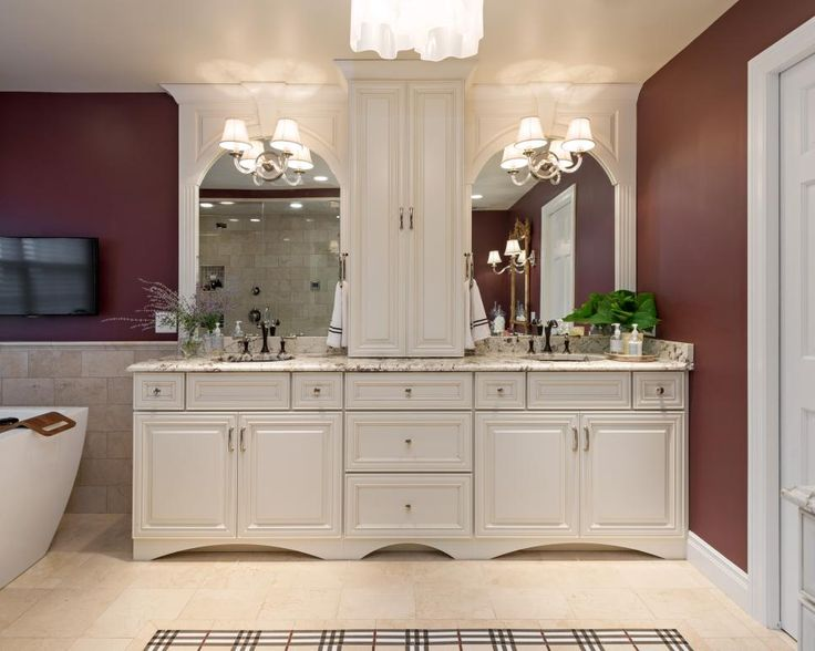 An elegant double vanity offers a his and hers space in this rich burgundy bathroom. A linen cabinet separates the two sinks to give a bit of privacy.