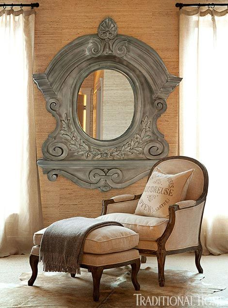 A linen chair and ottoman sit below a grand antique Belgian mirror - Traditional Home® / Photo: Eric Roth / Design: Joseph Abboud in partner with RH