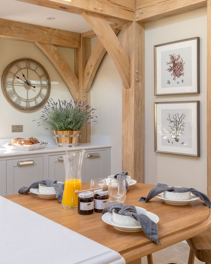 The rustic kitchen diner setting, antique-style metal framed wall clock and framed prints all add to the country charm in our modern Surrey barn project, whilst the soft colour scheme and vibrant lavender plant offer a enlivening, spring-like feel.