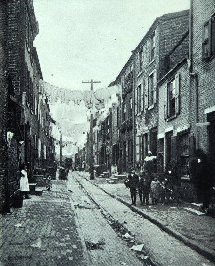 """SLUM DWELLINGS: 1905 near Starr-Garden, Philadelphia.    By 1910, Philadelphia tripled in population  to a little over a million and a half.   Along the southern edge of Center City, it was not unusual to find eight or nine families of immigrants crammed into three story rowhouses that were known as Philadelphia's """"horizontal slums,"""""""