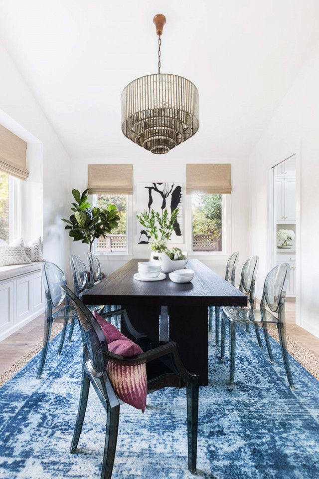 Dining room with a large blue rug, a black dining room table, acyclic dining room chairs, and a glass chandelier