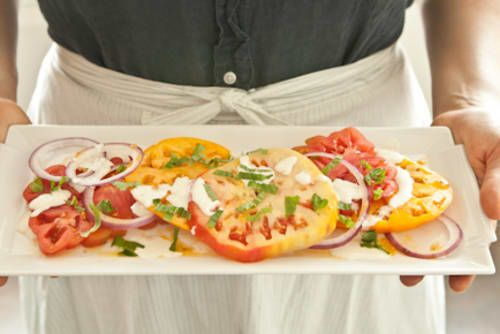 Coriander spiked basil-yogurt dressing classes up simple sliced tomatoes. Use a variety of tomato colors and sizes for most visual impact. You can make the dressing up to a day ahead, but slice and dress the tomatoes as close to serving time as possible.