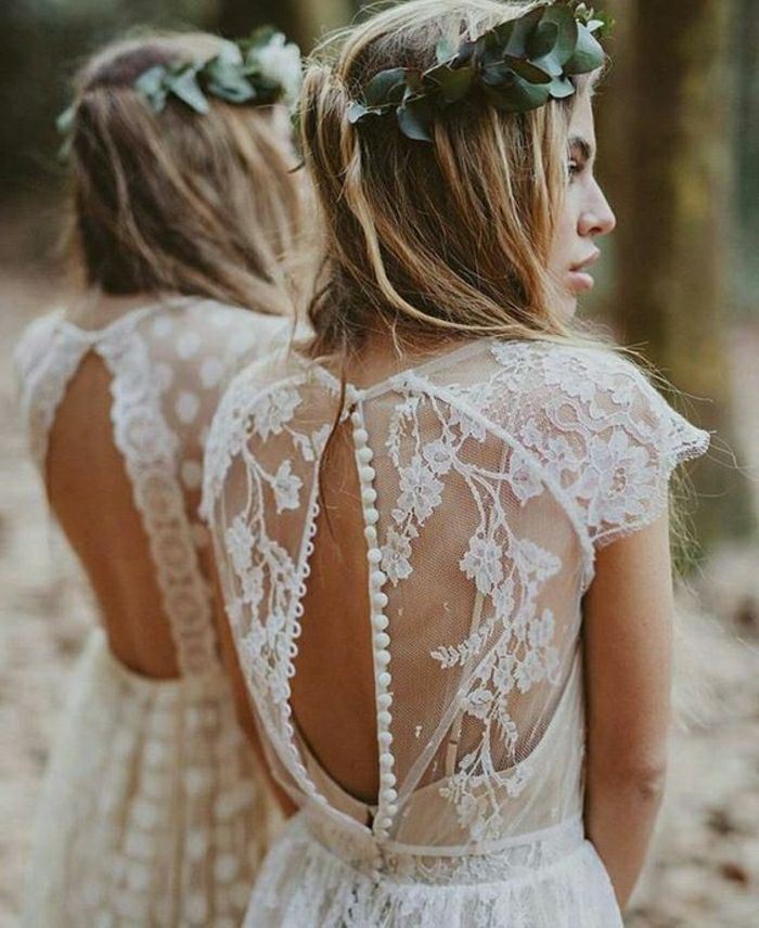 unique wedding dresses, blonde bride with green leaf crown facing sideways, in a white lace dress with unbuttoned sheer lace back, standing near a mirror