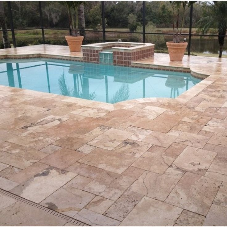 Noce Tumbled Travertine Outdoor Pavers grouted within a pool setting.