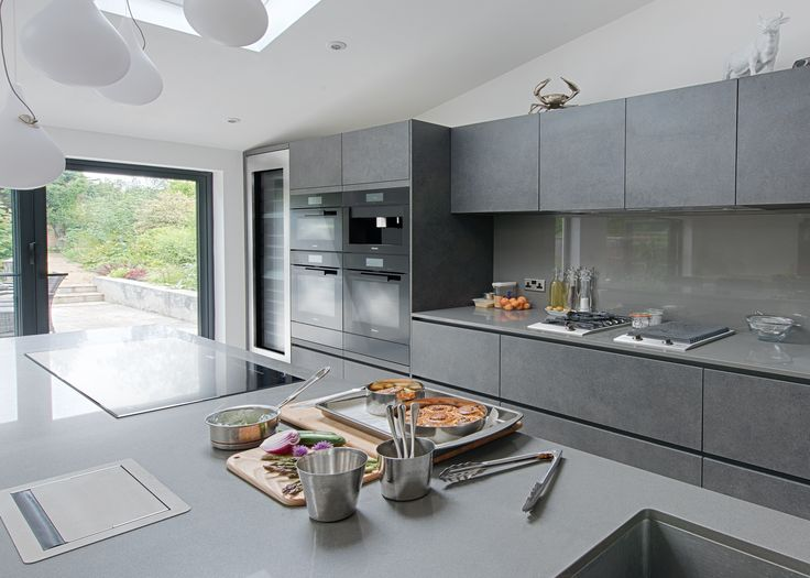 The large island in professional chef Monica Galetti's kitchen reflects the industrial style of the cabinets behind, and provides additional cooking and food preparation space, housing a Miele KM6381 Panoramic Induction Hob #kitcheninspiration