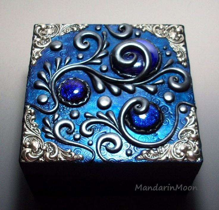 I decorated the top of this hinged wooden box with polymer clay and dichroic glass. The shimmery color comes from powdered pigments. They really pop on black clay! I own the copyright to this image...
