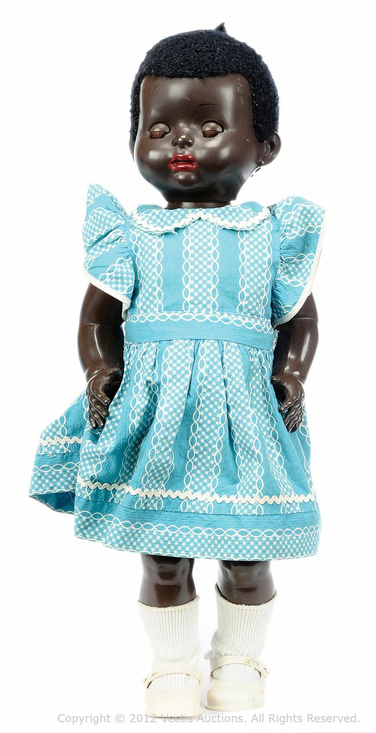 """21"""" walking Mandy Lou Delite toddler doll, with """"mama"""" noise mechanism and astrakhan wig, United Kingdom, 1953, by Pedigree. This earlier version of the Mandy Lou doll is easily identified by the seam across the palms of their hands. Although featuring a more ethnically authentic nose and mouth than earlier black dolls, any view of the progressive nature of the mold is weighted by the unnaturally red lip paint, clearly influenced by racist depictions in British film and minstrel shows."""