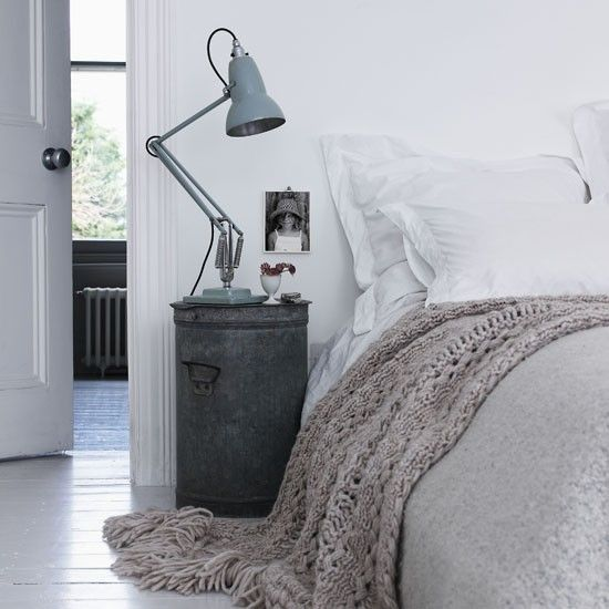 Rustic bedroom. An old galvanised bin looks rustic and chic as a bedside table in a clean, white bedroom, while the vintage lamp adds even more character. A chunky wollen throw softens the look. #Sleeptember