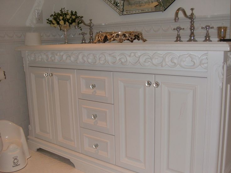 Custom vanity with decorative leaf molding detail.