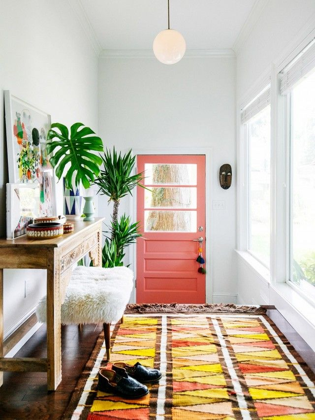 Bright entryway with a pink door, a retro light, a rug, and a furry ottoman