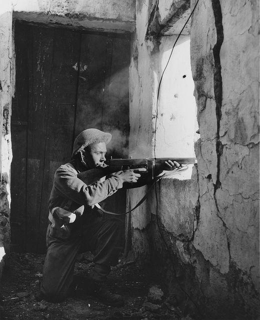 Un soldat canadien fait feu avec une mitraillette Thompson à travers une fenêtre