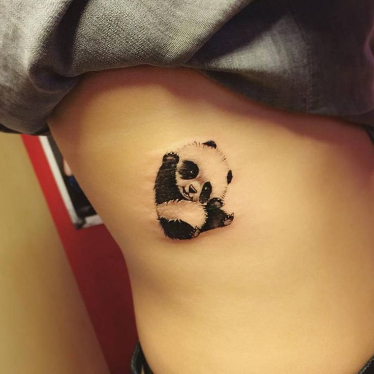 Illustrative panda tattoo on the right side ribcage.