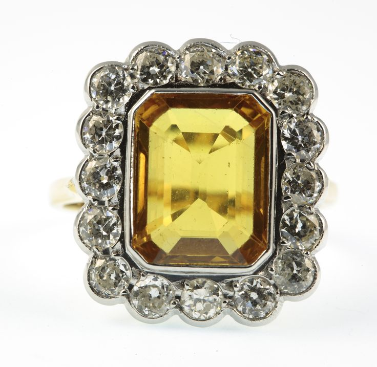 Lot 706, An 18ct yellow gold, yellow sapphire and diamond cluster ring, the rectangular centre stone approx 6ct surrounded by 16 brilliant cut diamonds approx 1.4ct, size P 1/2, est  £2000-2500