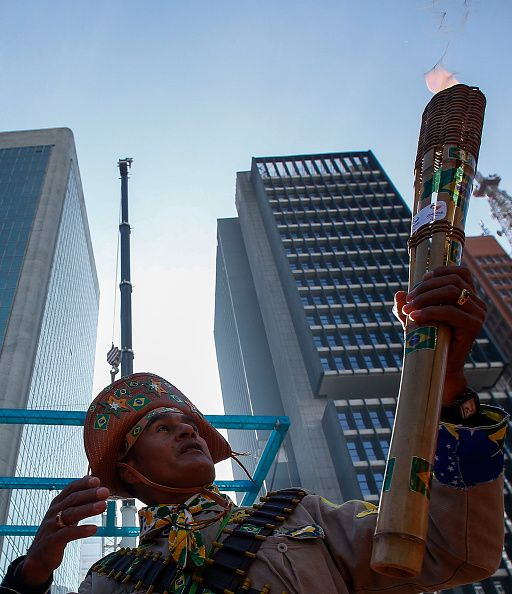 #RIO2016 A man makes a performance as the Olympic torch is carried along Paulista Avenue in Sao Paulo Brazil on July 24 2016 The Rio 2016 Olympic and...