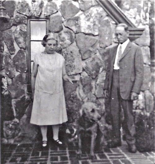 Laura and Manly are only around 65 and 75 here, and they are standing with their dog, Nero, in front of the little modern cottage where they lived for several years in Mansfield, Missouri.